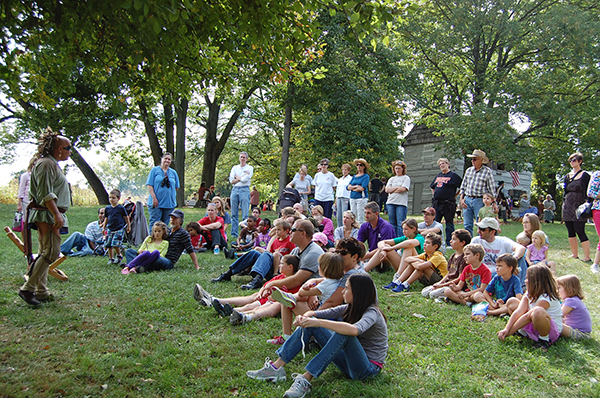 Visitors to Shawnee Lookout's annual Weekend in 1800s listen to a re-enactor on the log cabin lawn.