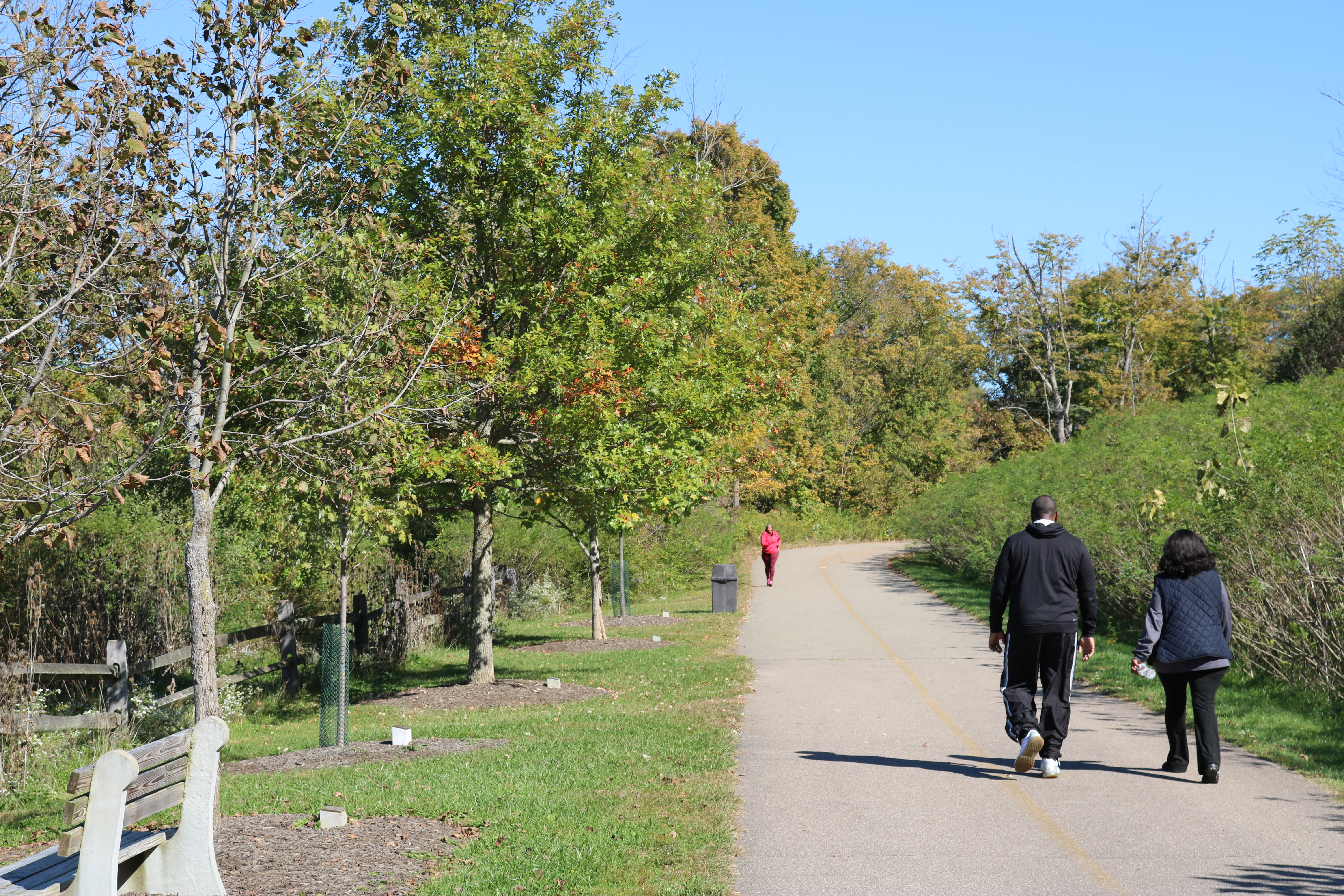 A couple walks along a paved, multi-use trail in Winton Woods.