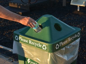 An individual recycles their water bottle in a recycling bin.
