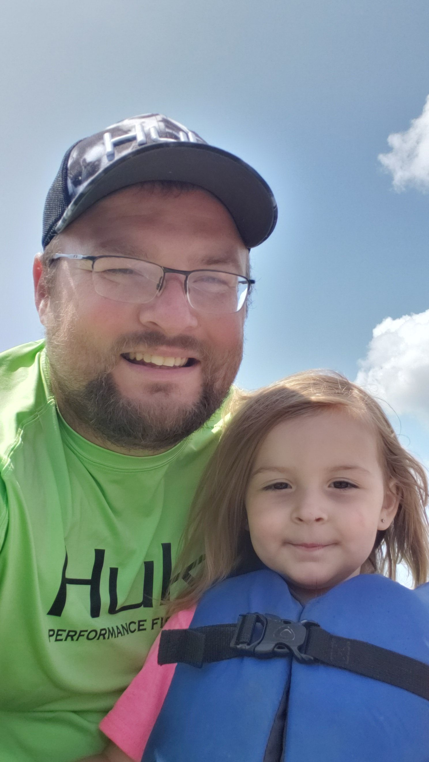 Brian McLucas and his daughter Addilyn smile outside. Addilyn is wearing a life vest and the blue sky is behind them.