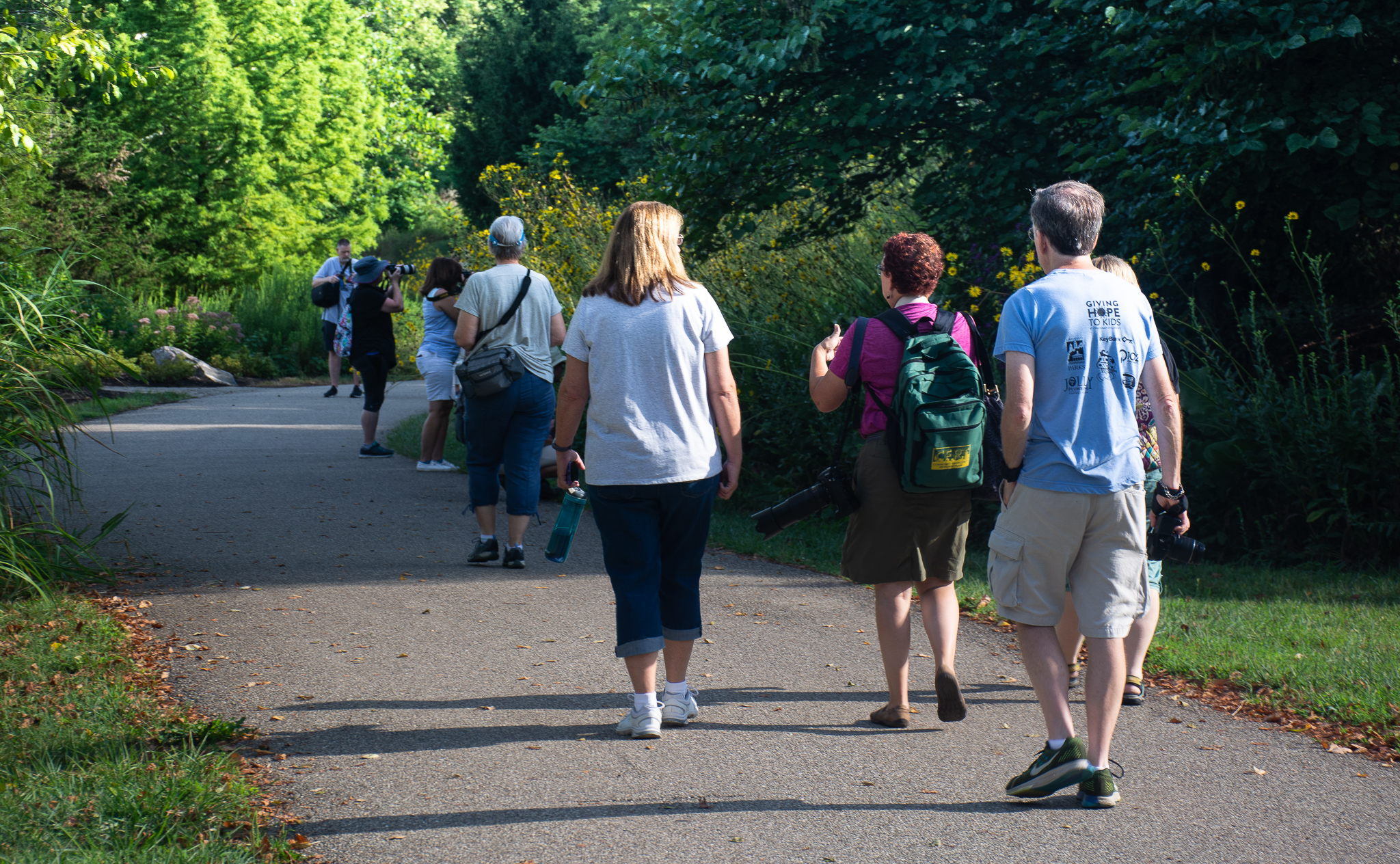 A group of adults walks down a paved trail. With cameras and water bottles in hand, everyone is prepared to take a snapshot during this sunny afternoon.
