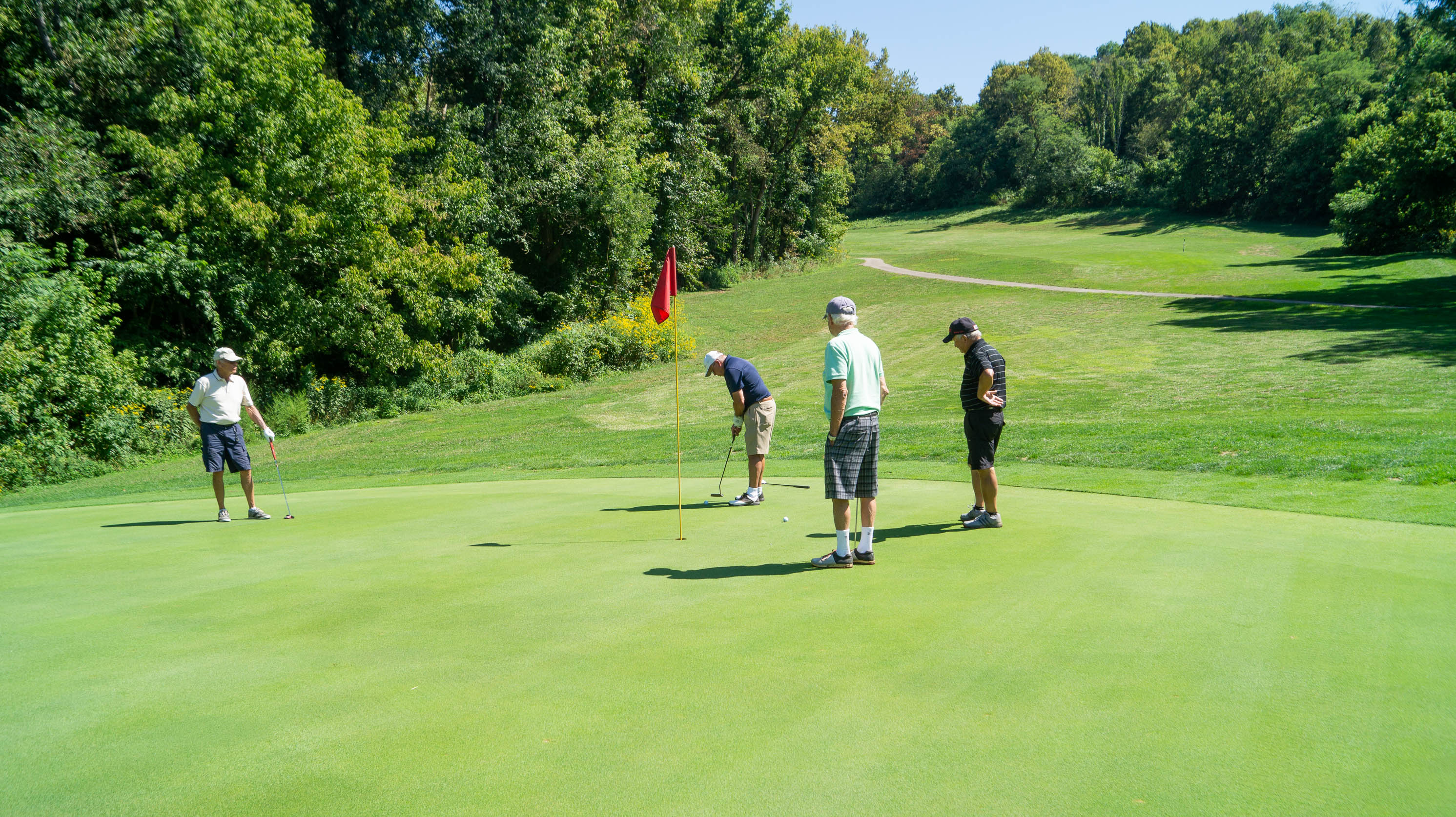 A group of four men tee off at Shawnee Lookout Golf Course during its final season. From the left, clockwise: a man in a white shirt and navy shorts waits for his teammates to finish their round; in the middle, a man with a navy shirt and khaki shorts is putting close to the hole; and two men, one in a turquoise shirt and plaid shorts, and the other in a black striped shirt and black, shorts look on. The hole is surrounded by trees on a sunny day.