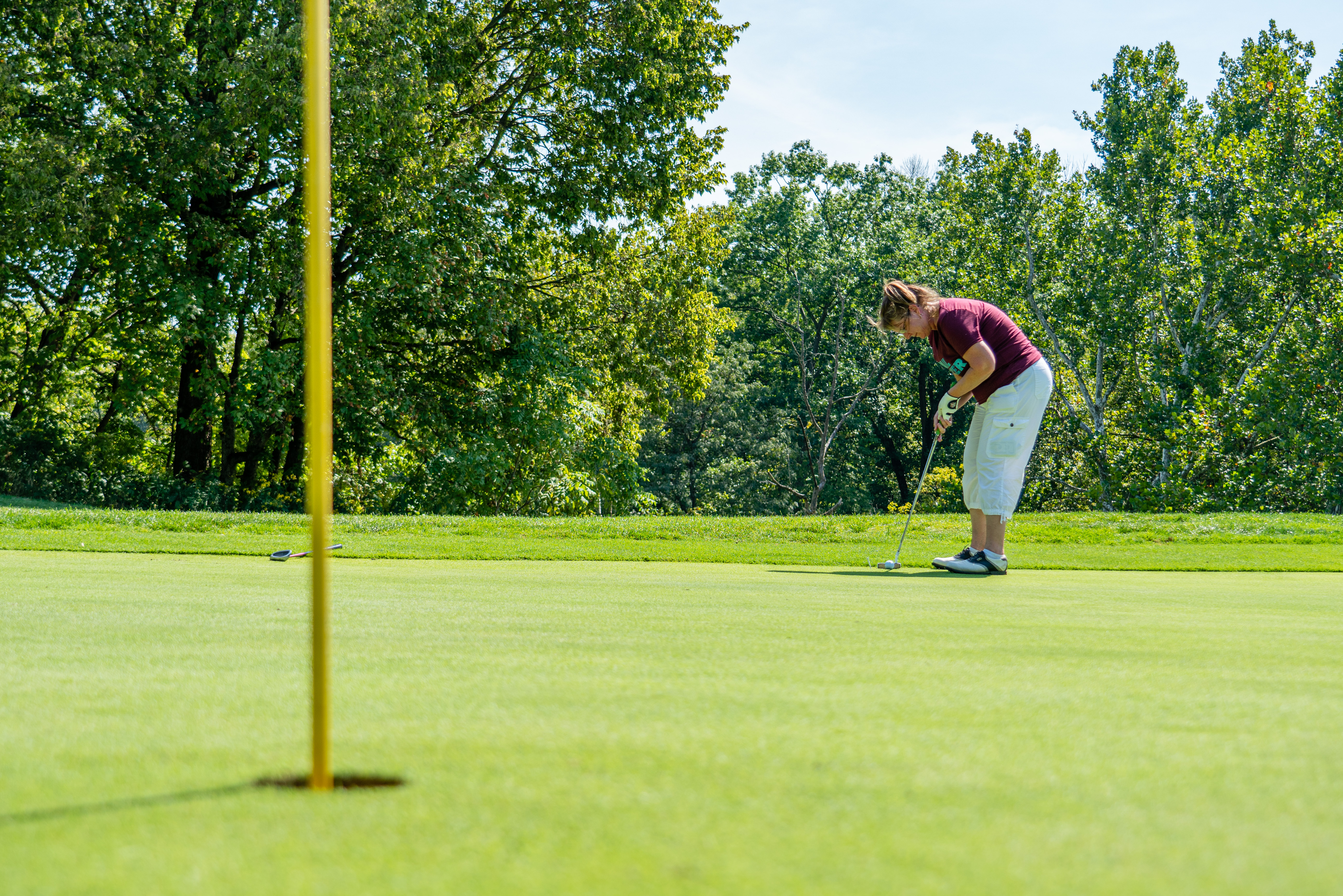 A woman in a maroon shirt and khaki pants is golfing on the green close to the hole at Shawnee Lookout Golf Course.