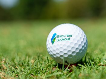 A golf ball with the Great Park logo and the name Shawnee Lookout on it sits in the green.