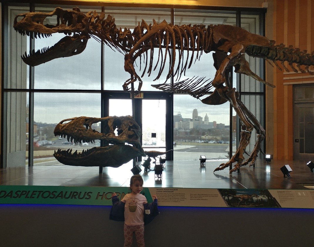 A young girl poses in front of a Tyrannosaurus rex fossil at Cincinnati Museum Center.
