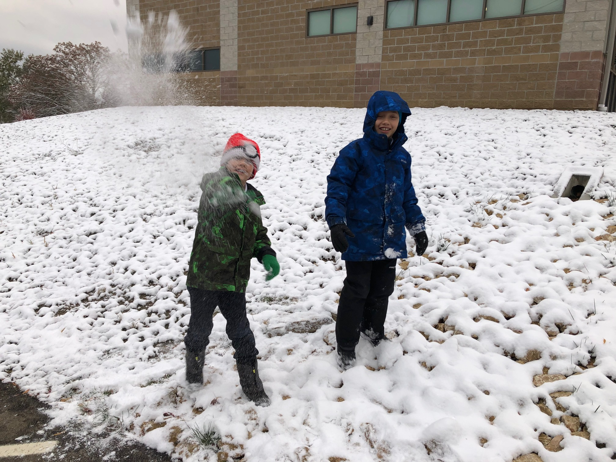 Two young boys throw snowballs and play in the snow.