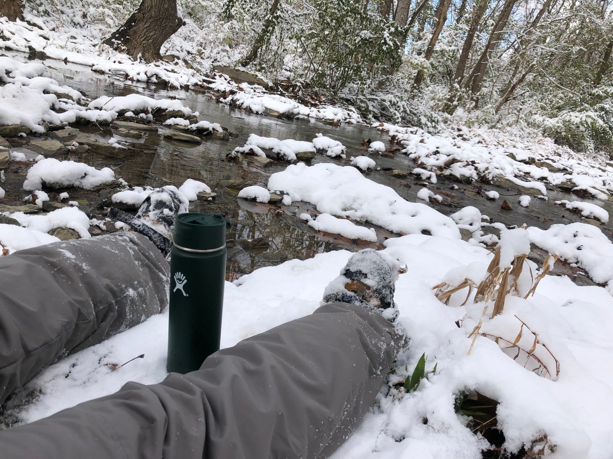 A woman sits down in the snow with her canteen next to the creek at Richardson Forest Preserve.