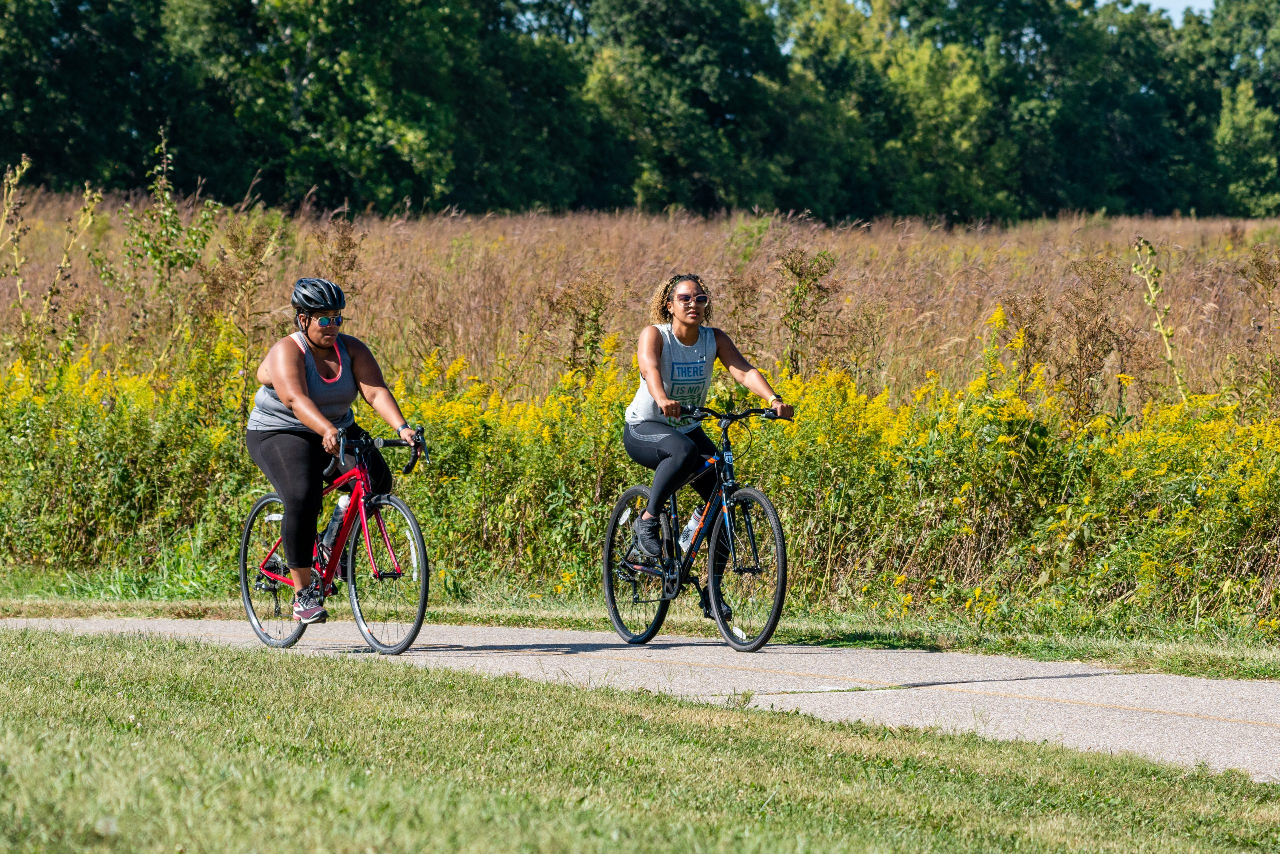 Two women ride their bicycles at a park on a sunny day.