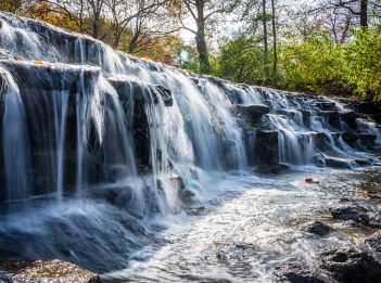 A long exposure photograph of Buckeye Falls at Sharon Woods. It is a sunny fall day.