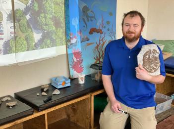 Nature Interpreter Tom Hughes holds up a fossil inside Sharon Centre