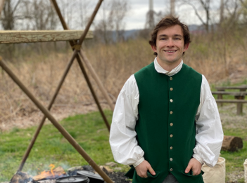 Nature Interpreter Will Buelsing stands in front of his cooking fire in pioneer garb.