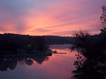 The sun rises over the Miami Whitewater Forest Boathouse, creating a pink and purple sky.