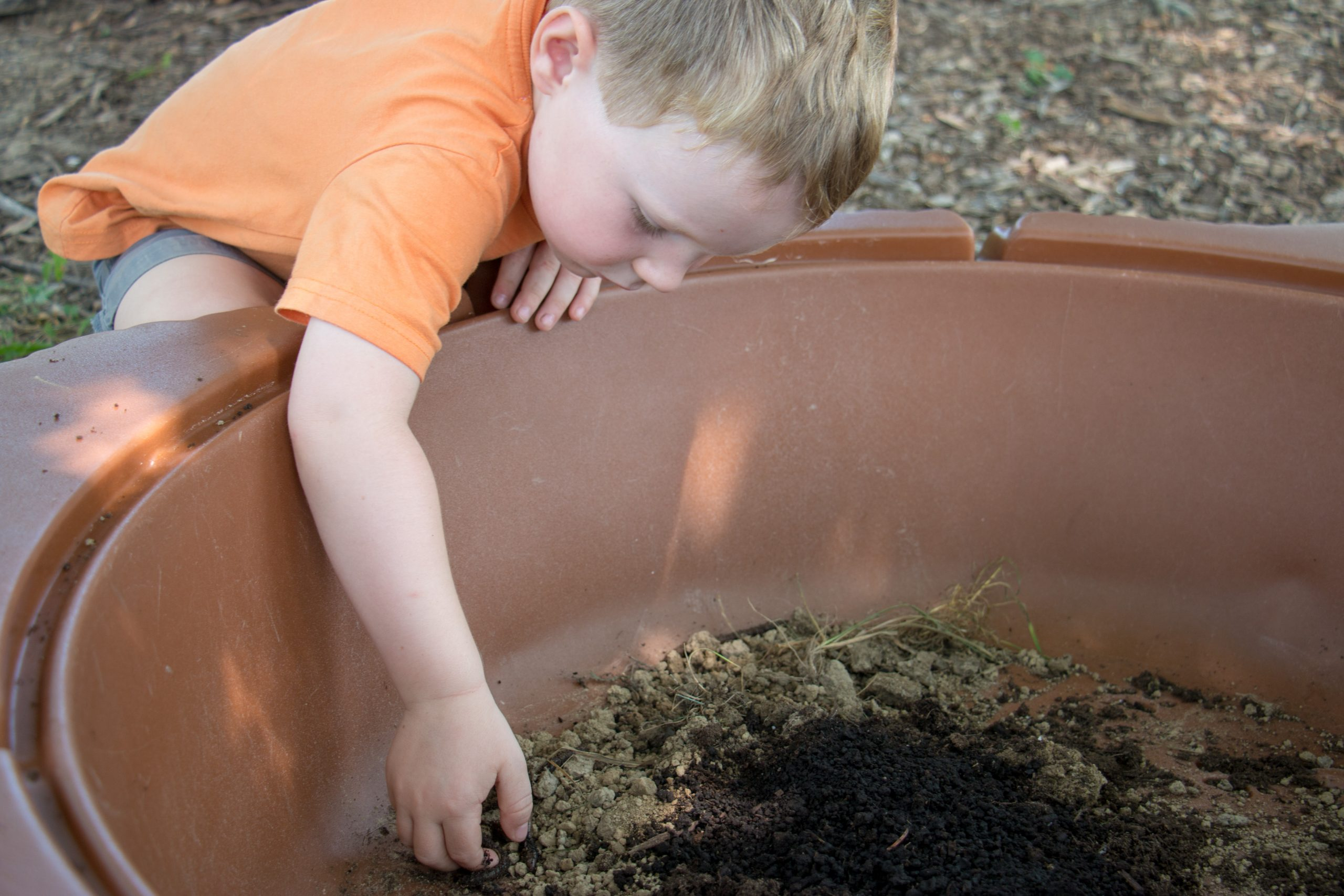A young boy digs into dirt and mud. It is sunny.