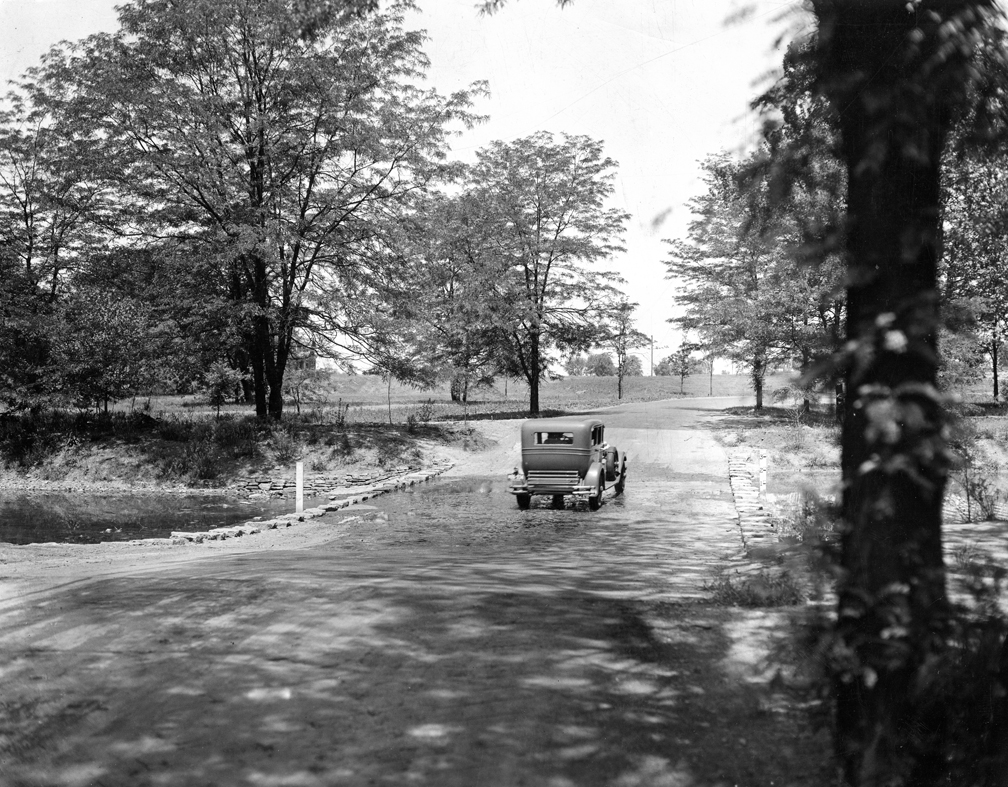 An antique car drives on a dirt road, the former entrance to Sharon Woods.