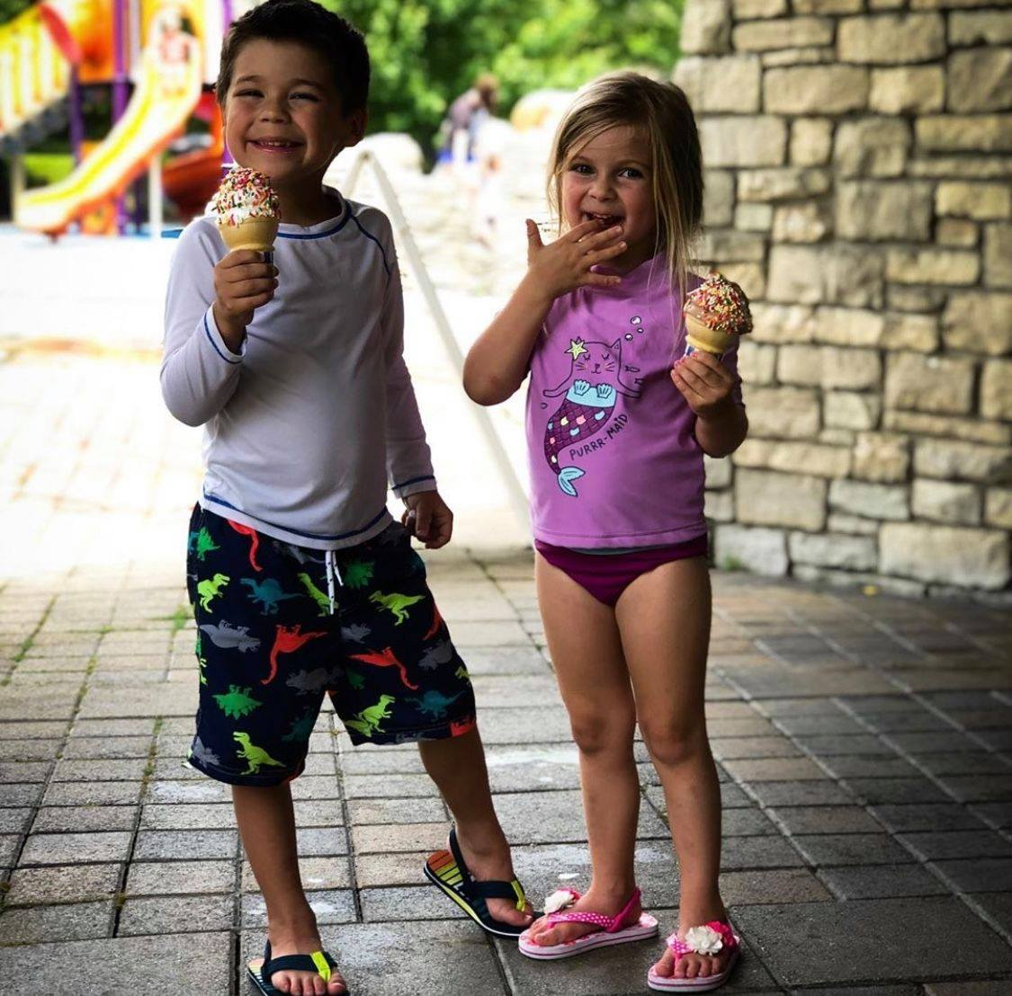 A young boy and a young girl enjoy ice cream on a sunny day.