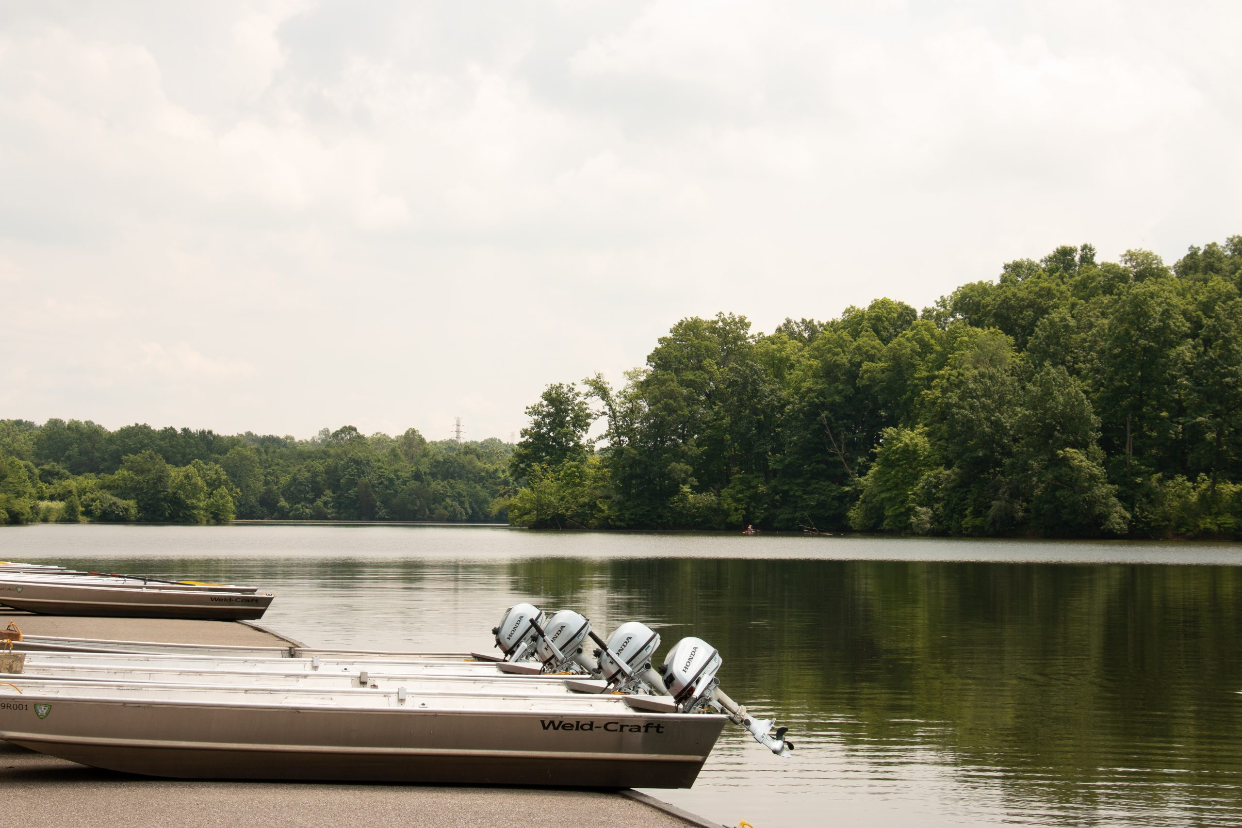 Boats line the shore of Miami Whitewater Forest Lake during a sunny summer day.