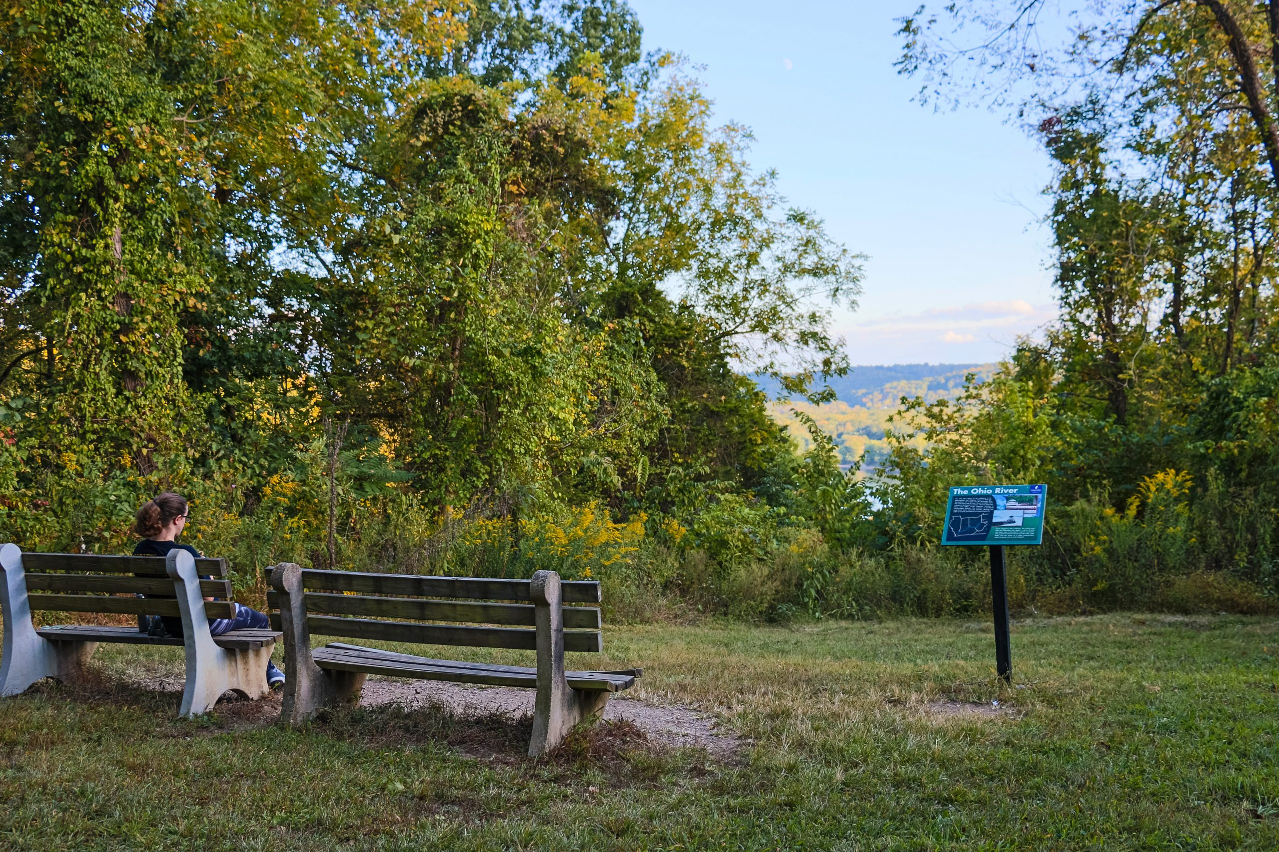 A woman sits on a bench overlooking the Ohio River at Withrow Nature Preserve.