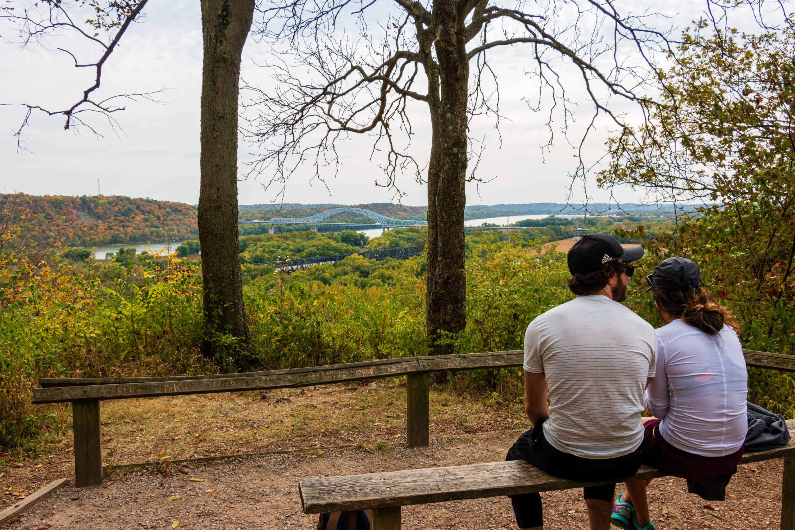 A couple sits on a bench on the Miami Fort Trail, overlooking the confluence of the Great Miami and Ohio rivers.