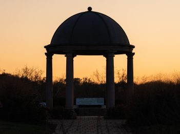 The sun sets over a gazebo, making the sky orange.
