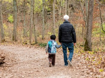 A man and young boy walk on a forest trail on a fall afternoon.
