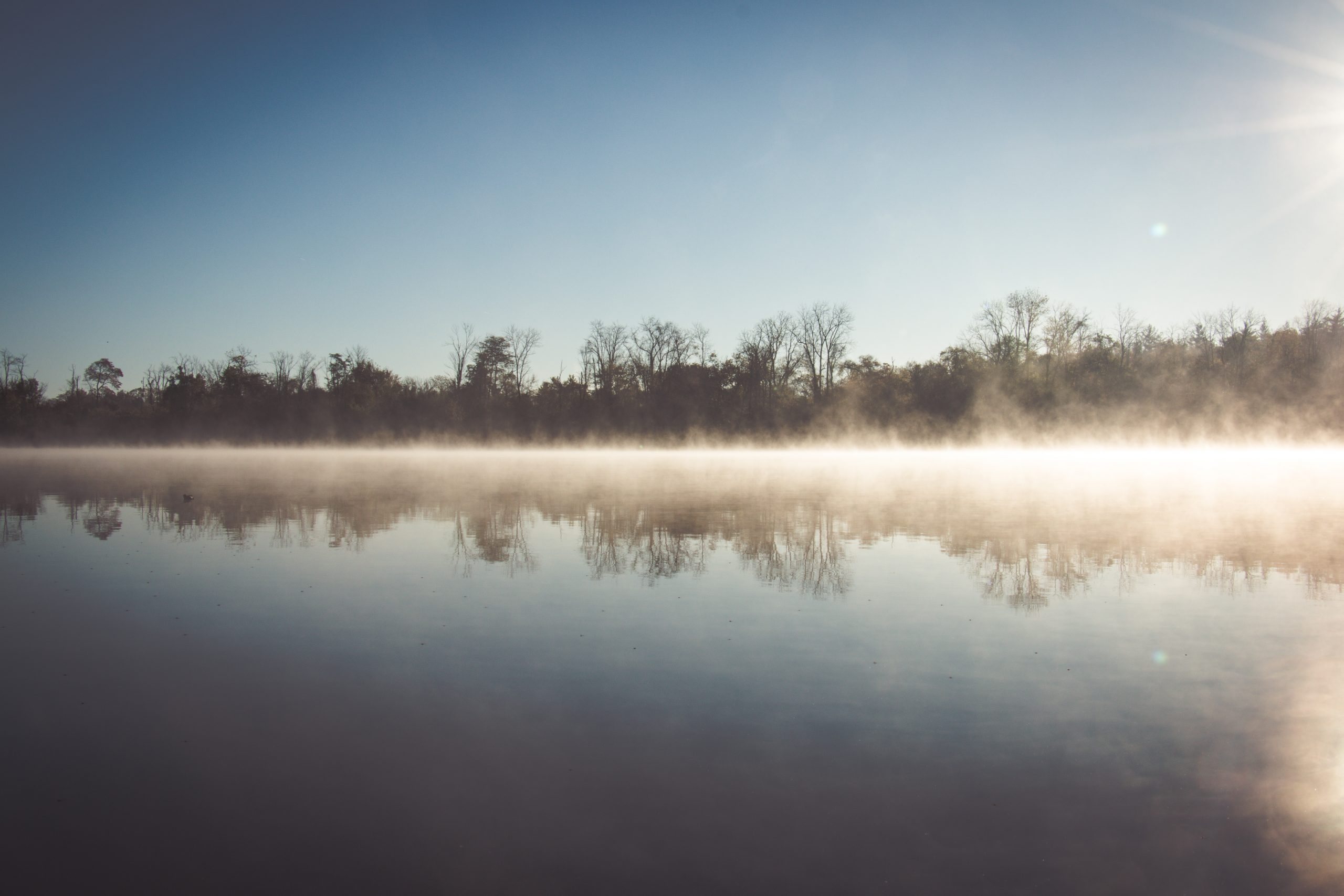 The sun shines over Winton Lake. You can see the reflection in the water of the trees lining the lake. There is fog permeating from the surface of the water.