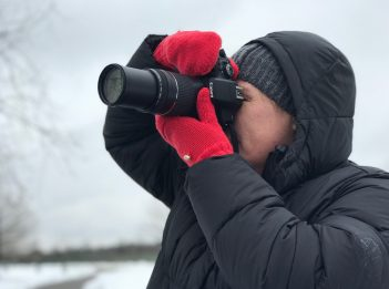 A person wears red mittens, a black coat and a black hat while taking a photo with his camera on a snowy winter day.