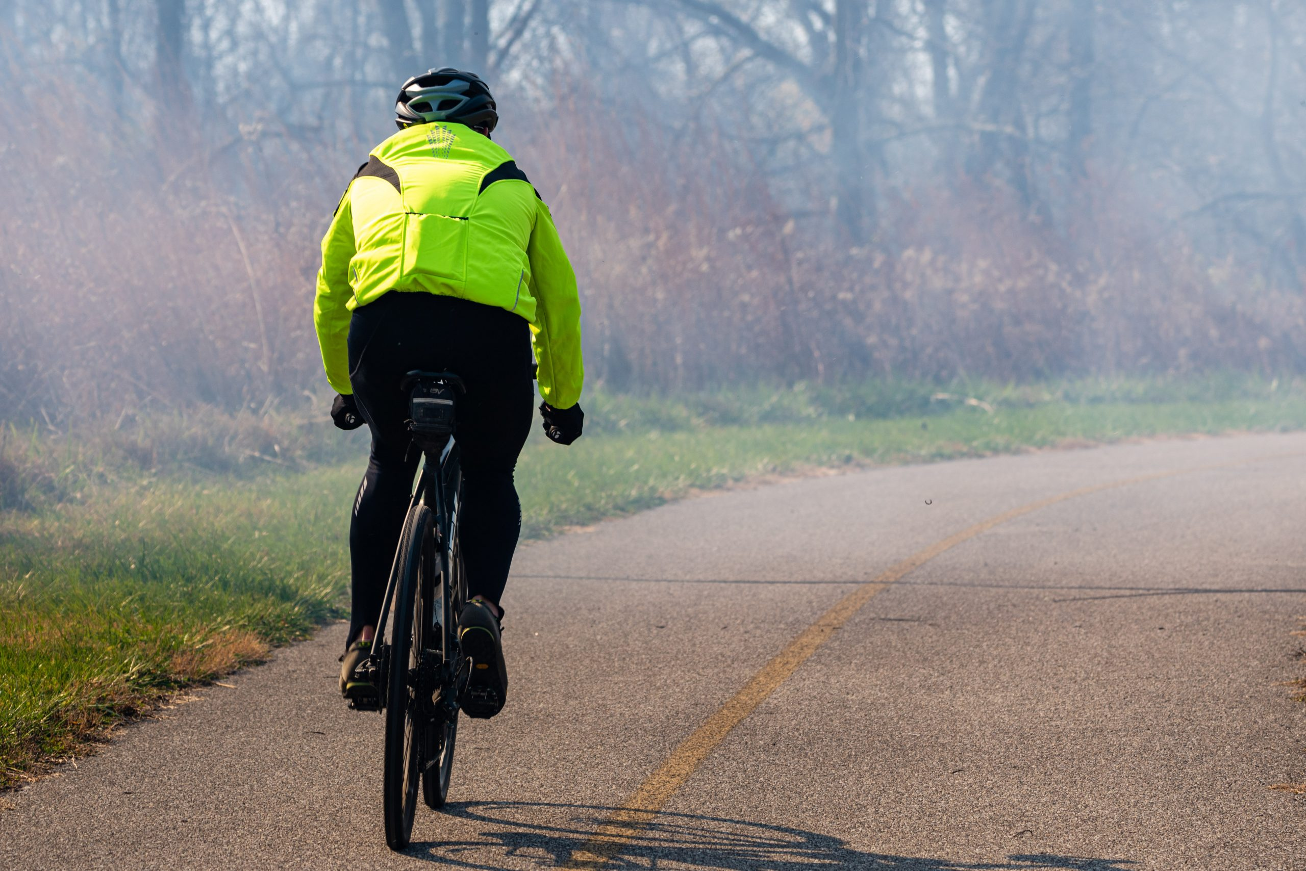A person in neon yellow jacket rides a bike on the paved trail at Miami Whitewater Forest.