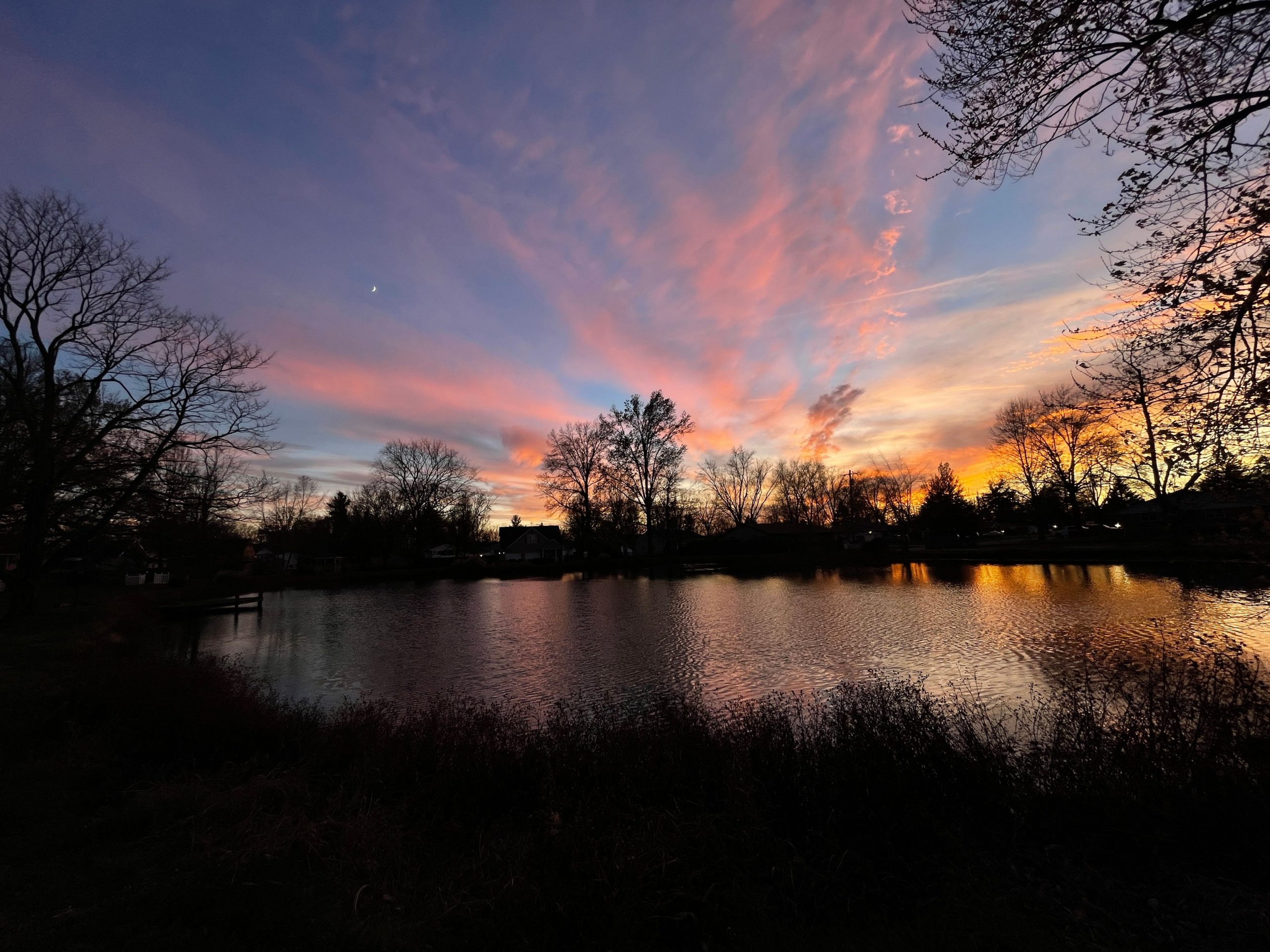 The sun sets over a lake, making the sky a vibrant blue. The clouds vary in color from light pink to orange and yellow.