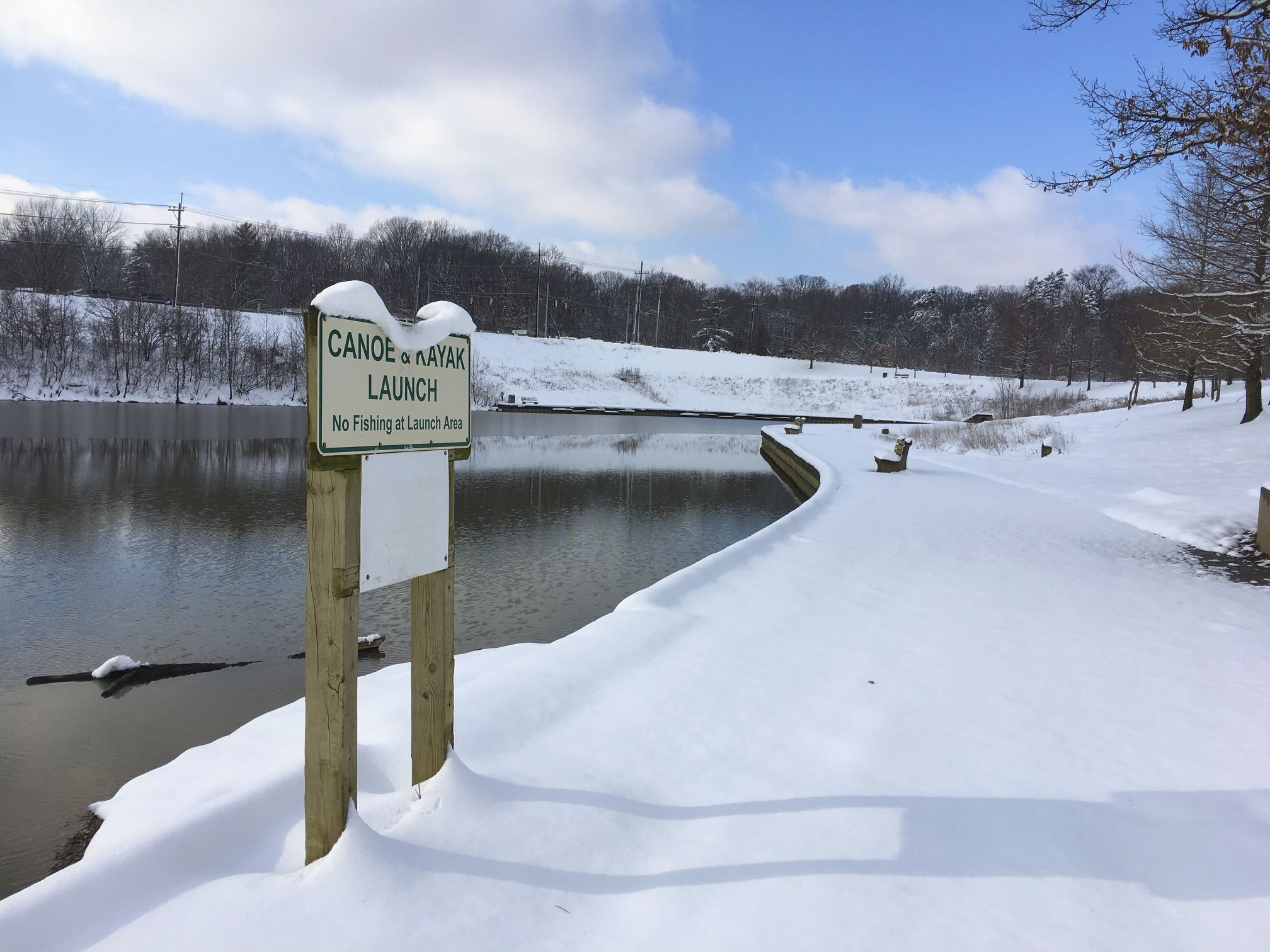 A canoe and kayak launch sign is covered in snow while the lake behind it is frozen. All the benches and path surrounding the lake are also covered in snow.