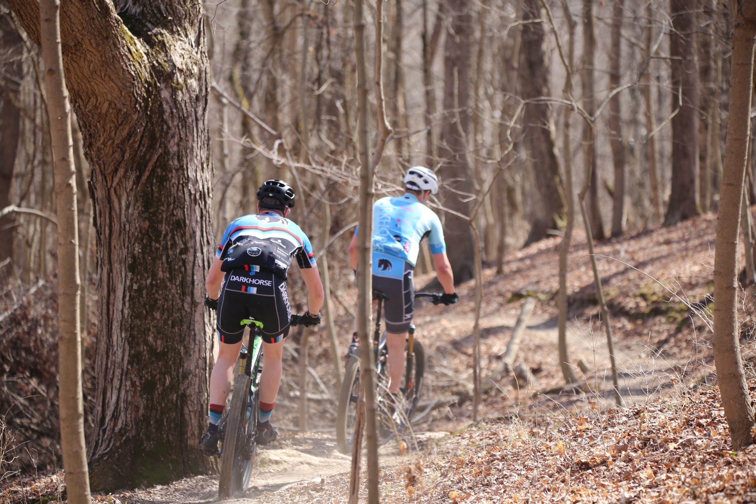 Two individuals ride their mountain bikes on the mountain bike trail at Mitchell Memorial Forest.
